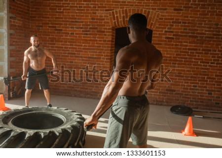 African and caucasian sports friends training with sledge hammer hitting it on large and heavy tire. Concept workout, crossfit endurance and strength. #1333601153