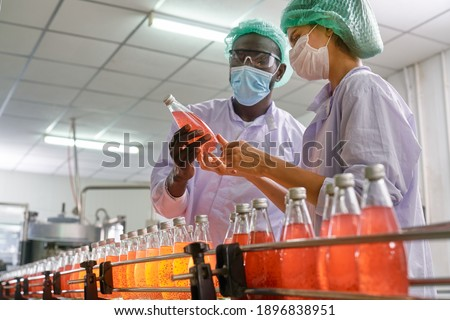African and European specialists of beverage check quality of red juice in automatically product line of beverage industry