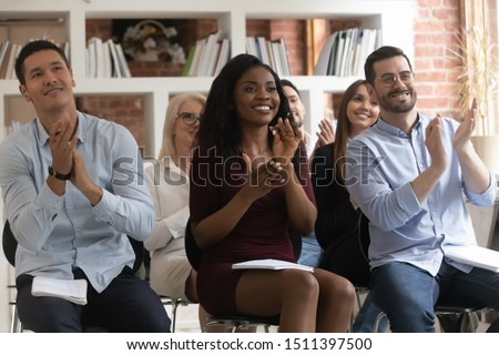 African asian european entrepreneurs multinational business people sitting on chairs in row seminar participants clap hands expressing gratitude for speech, corporate training and coaching concept