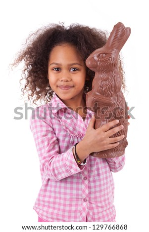 African Asian girl holding a giant chocolate rabbit, isolated on white background