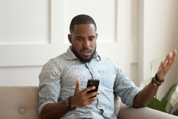African astonished man sitting on sofa holds cellphone read e-mail sms feels shocked received terrified news, guy looks at online calendar forgot missed important meeting, phone crash problems concept