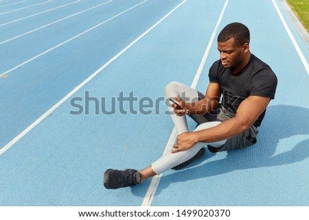 african attractive sportsman using smart phone while sitting on the running track. full length photo. rest time, free time , spare time. copy space
