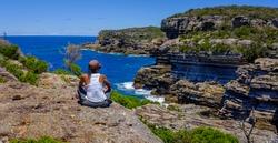 African Australian woman enjoying the dramatic coastal sea view and cliffs at Mermaids inlet, Beecroft Head, Abrahams Bosom Reserve, Jervis Bay, NSW, Australia