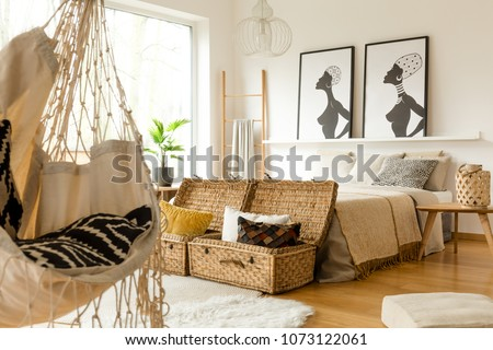 African bedroom interior with a swing, boxes with pillows, double bed and posters #1073122061