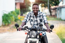 African biker riding a motorcycle with smile and happy