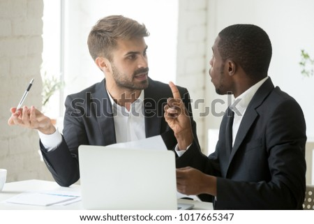 African black client having claims about business document disagreeing with caucasian partner, stressed diverse businessmen arguing in office disgruntled by bad contract or obligations noncompliance