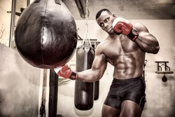 African black male boxer punching ball wearing boxing gloves in gym