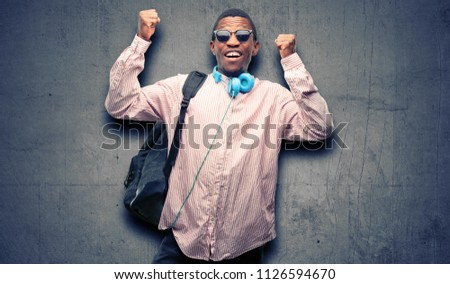 African black man student happy and excited celebrating victory expressing big success, power, energy and positive emotions. Celebrates new job joyful #1126594670