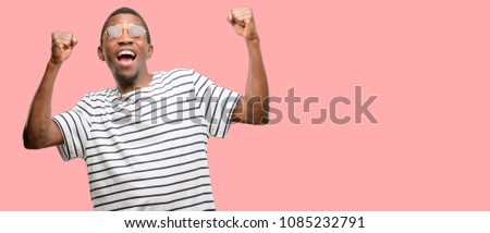 African black man wearing sunglasses happy and excited celebrating victory expressing big success, power, energy and positive emotions. Celebrates new job joyful