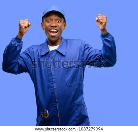 African black plumber man happy and excited celebrating victory expressing big success, power, energy and positive emotions. Celebrates new job joyful #1087279094
