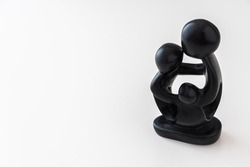 African black wooden figure of a family hugging each other. Isolated on white background with copy space.