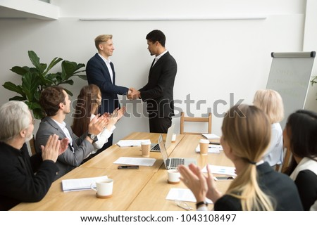 African boss handshaking caucasian subordinate congratulating with promotion, appreciating good work result, team supporting applauding black ceo and white employee shaking hands at group meeting