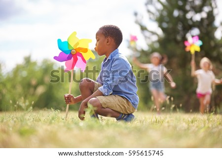 African boy and friends with pinwheels playing at the park - Shutterstock ID 595615745
