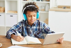 African boy in headphones using digital tablet and making notes in his notebook while sitting at the table at home