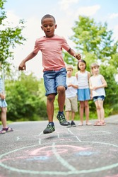 African boy playing hopscotch and jumping with ambition and concentration