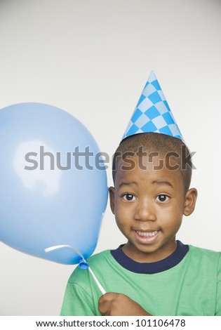 African boy wearing party hat and holding balloon