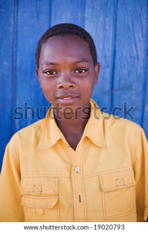 african boy with yellow shirt, in a village near Kalahari desert