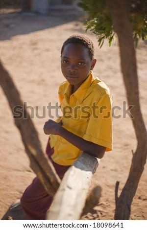 african boy with yellow shirt sitting in the shade in a village near Kalahari desert - stock photo