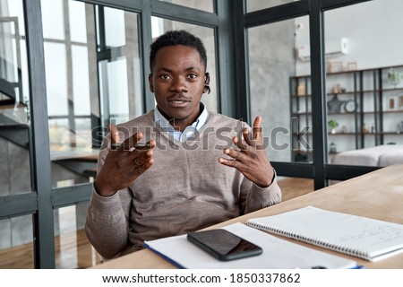 African business man, coach, executive wearing headset talking to camera conference video calling, giving webinar, online class, distance teaching or working at home office, web cam view. Headshot.