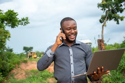 african business man making a phone call,holding a laptop, feeling happy