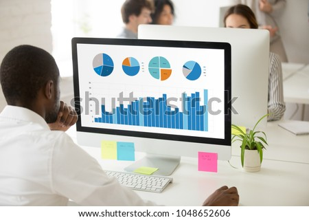 African businessman analyzing graphic data charts graphs of marketing sales project performance on pc monitor in office, black employee preparing statistical report with application or online service