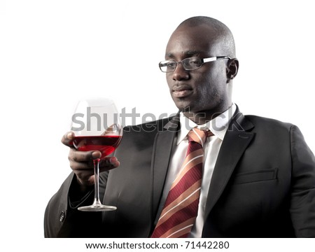 African businessman holding a glass of wine