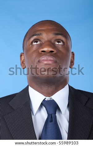 African businessman looking up to the copy space (blue background)