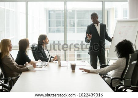 African businessman presenting new project to partners, black coach giving presentation to clients at conference meeting room, dark skinned team leader reporting about work result with whiteboard