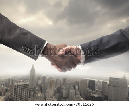African businessman's hand shaking white businessman's hand with cityscape on the background