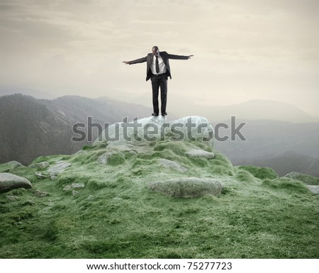 African businessman standing with open arms on a rock