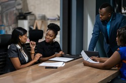 African businessman talking with a diverse group of female colleagues while having a meeting together around a table in an office boardroom