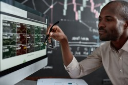 African businessman, trader sitting in front of computer screen and holding glasses while looking at graph chart. Blackboard full of data analyses in the background. Stock trading, people concept.