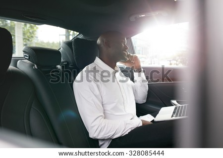 African businessman with laptop talking on mobile phone inside a car. Young entrepreneur working during travelling to office in a luxury car.