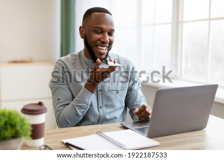 African Businessman With Smartphone Using Voice Assistant App Or Loudspeaker Talking Holding Phone Near Mouth Sitting At Workplace In Modern Office. IOT, Business Applications And Voice Search