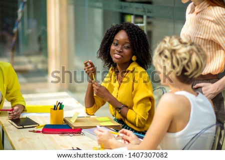 african charming woman gets pleasure from chatting with friends in the room with modern interior