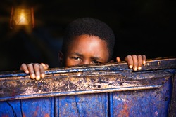 african child behind the wooden wall in the night in a  house in an African village in Botswana