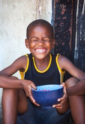 African child portrait in a village in the rural  Botswana eating  in front of the house