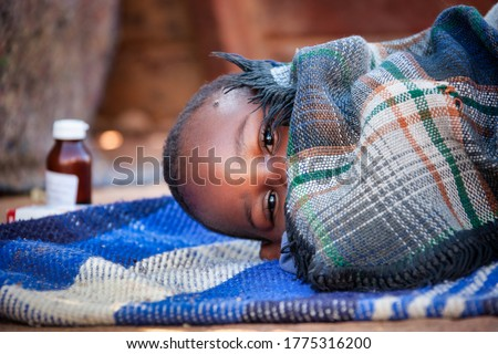 african child toddler sick with malaria medicine in the background, laying down on a blanket in the yard Foto d'archivio ©