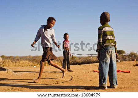 african children jumping rope in the sand, Mmankodi village Botswana