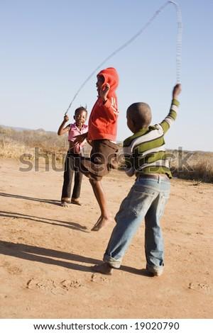 african children jumping rope in the sand, Mmankodi village Botswana