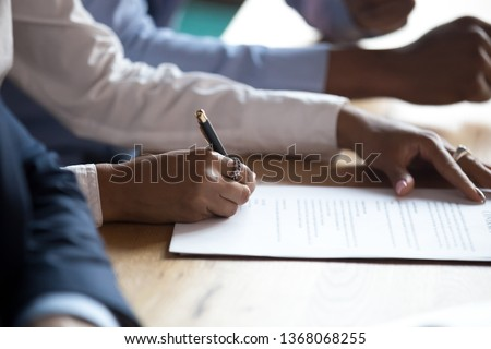 African client customer hand sign business contract at meeting, get hired make sale purchase deal write signature on document employment agreement, take bank loan buy insurance service, close up view