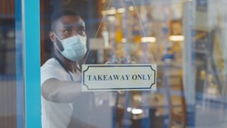 African coffee shop owner in medical mask and gloves hanging take away only sign on front door. Young afro entrepreneur opening cafe only for take away orders. Small business during quarantine concept