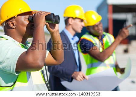 african construction worker using binoculars looking at construction site #140319553