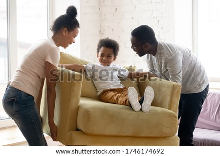 African couple carrying armchair where sit adorable small toddler son. Happy family placing delivered furniture bought in modern store, furniture shop advertisement, relocation day at new home concept Сток-фото ©