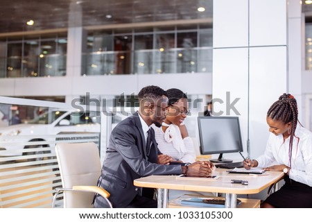 african couple getting car key from car dealer in showroom and signing contract