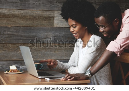African couple having coffee at a cafe: black girl sitting in front of laptop pointing at the screen and laughing, looking through wedding photos together with her husband who is standing next to her