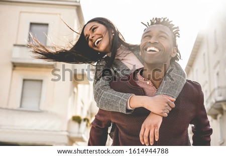 African couple having fun outdoor in city tour - Young people lovers enjoying time together during vacation journey - Love, fashion, travel and relationship concept - Focus on man face ストックフォト ©