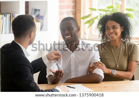 African couple property renters or buyers receive keys from real estate agent male, signing agreement contract good offer, first home new house, loan mortgage, relocation construction industry concept
