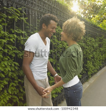 African couple smiling at each other outdoors