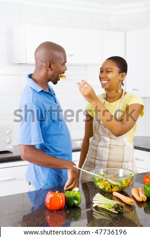 african couple tasting food in kitchen